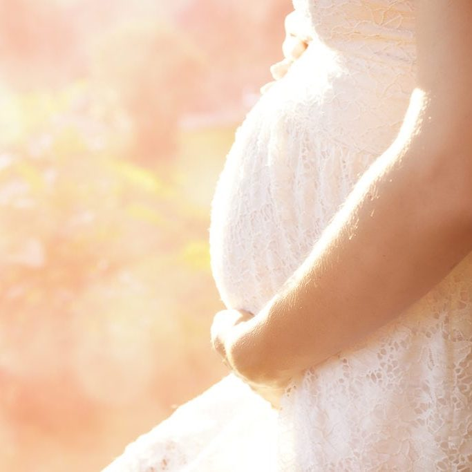schwangere Frau im weißen Kleid